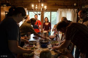 People gathered in a home standing around a table reaching for food to fill their plates